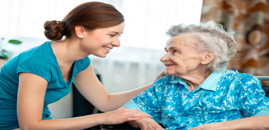 Image of care worker assisting elderly woman with writing. The background looks like a home.